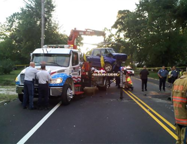 TRUCK IS LIFTED OFF THE CAR AND RAISED for  investigators TO INSPECT STEERING DAMAGE